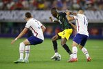 United States defender Sam Vines (3) and midfielder Sebastian Lletget (17) pressure Jamaica forward Blair Turgott (15) as he handles the ball in the first half of a 2021 CONCACAF Gold Cup quarterfinals soccer match, Sunday, July 25, 2021, in Arlington, Texas. (AP Photo/Brandon Wade)