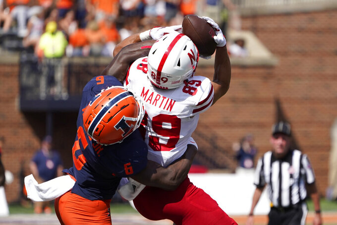 Nebraska wide receiver Oliver Martin catches a pass from quarterback Adrian Martinez as Illinois defensive back Tony Adams defends during the second half of an NCAA college football game Saturday, Aug. 28, 2021, in Champaign, Ill. Illinois won 30-22. (AP Photo/Charles Rex Arbogast)