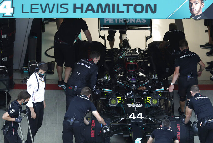 Crew work on the car of Mercedes driver Lewis Hamilton of Britain during the qualifying session for the upcoming Russian Formula One Grand Prix, at the Sochi Autodrom circuit, in Sochi, Russia, Saturday, Sept. 26, 2020. The Russian Formula One Grand Prix will take place on Sunday. (AP Photo/Pavel Golovkin, Pool)