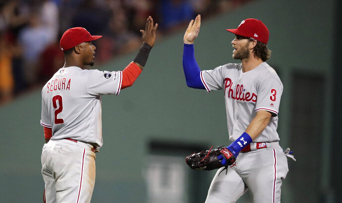 Philadelphia Phillies shortstop Jean Segura (2) is congratulated by Bryce Harper after the team's 3-2 win against the Boston Red Sox in a baseball game at Fenway Park in Boston, Tuesday, Aug. 20, 2019. Segura had a two-run double in the first. (AP Photo/Charles Krupa)