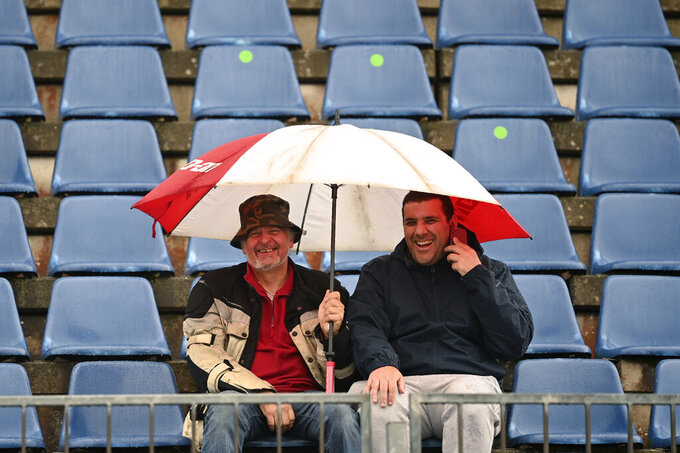 Fans on the stands endure the rain as bad weather delays the start of the first practice session for the Eifel Formula One Grand Prix at the Nuerburgring racetrack in Nuerburg, Germany, Friday, Oct. 9, 2020. The Germany F1 Grand Prix will be held on Sunday. (Ina Fassbender, Pool via AP)
