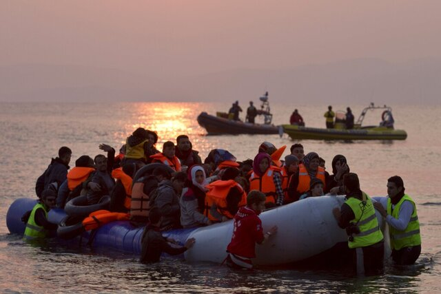 FILE - In this Sunday, March 20, 2016 file photo, volunteers help migrants and refugees on a dinghy as they arrive on the shore of the northeastern Greek island of Lesbos, after crossing the Aegean sea from Turkey. A Washington-based Syrian rights group filed on Thursday, Jan. 28, 2021 a case with the International Criminal Court calling for an investigation into alleged crimes against humanity by Greece for its treatment of refugees at its borders and in sprawling camps. (AP Photo/Petros Giannakouris, File)