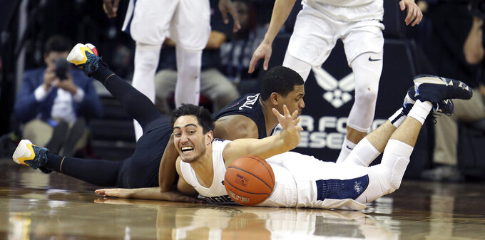 San Diego State's Matt Mitchell, left, and Utah State's Abel Porter dive for a loose ball during the first half of an NCAA college basketball game in the Mountain West Conference men's tournament championship Saturday, March 16, 2019, in Las Vegas. (AP Photo/Isaac Brekken)