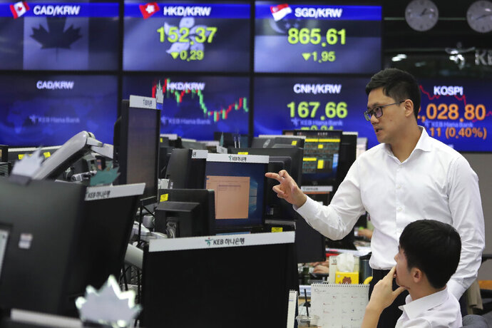 Currency traders work at the foreign exchange dealing room of the KEB Hana Bank headquarters in Seoul, South Korea, Monday, Oct. 7, 2019. Asian shares were mixed Monday, following a healthy report on U.S. jobs, while investors cautiously awaited the upcoming trade talks between the U.S. and China. (AP Photo/Ahn Young-joon)