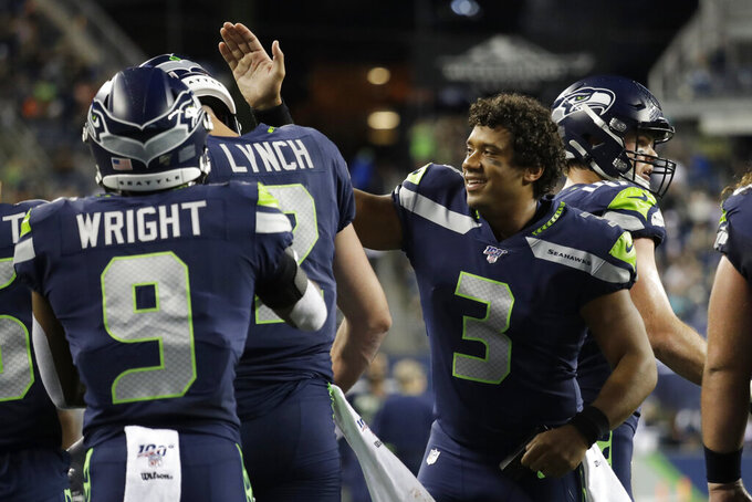 Seattle Seahawks quarterback Russell Wilson (3) greets backup quarterback Paxton Lynch, second from left, after Lynch scored a touchdown against the Denver Broncos during the second half of an NFL football preseason game Thursday, Aug. 8, 2019, in Seattle. (AP Photo/Elaine Thompson)