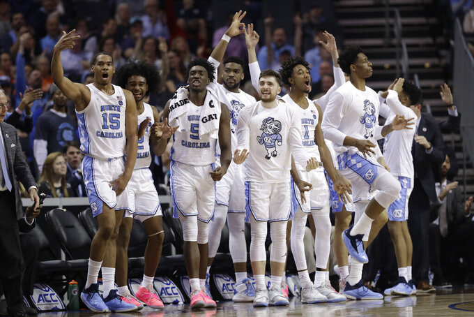 North Carolina players celebrate a teammate's basket against Louisville during the second half of an NCAA college basketball game in the Atlantic Coast Conference tournament in Charlotte, N.C., Thursday, March 14, 2019. (AP Photo/Chuck Burton)