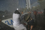 A Catholic nun is drenched by police water cannons used to disperse anti-government demonstrators protesting over inequality two days before Chileans will decide whether or not to rewrite the constitution that dates back to the dictatorship of Augusto Pinochet, in Santiago, Chile, Friday, Oct. 23, 2020. Amid a year of contagion and turmoil, Chileans turned out two days later to vote overwhelmingly in favor of having a constitutional convention draft a new charter to replace guiding principles imposed four decades ago under Pinochet. (AP Photo/Esteban Felix)