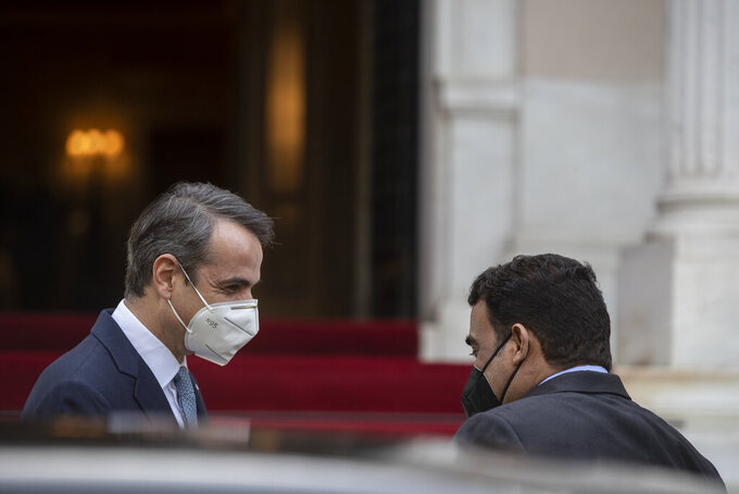 Greek Prime Minister Kyriakos Mitsotakis, left, welcomes the head of the Presidential Council of Libya Mohamed al-Menfi before their meeting, in Athens, on Wednesday, April 14, 2021. (AP Photo/Petros Giannakouris)