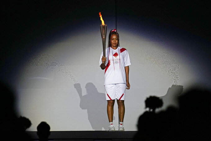 FILE - In this July 23, 2021 file photo, Japan's Naomi Osaka holds the Olympic torch during the opening ceremony in the Olympic Stadium at the 2020 Summer Olympics, in Tokyo, Japan. Osaka and Simone Biles are prominent young Black women under the pressure of a global Olympic spotlight that few human beings ever face. But being a young Black woman -- which, in American life, comes with its own built-in pressure to perform -- entails much more than meets the eye. (AP Photo/Natacha Pisarenko, File)