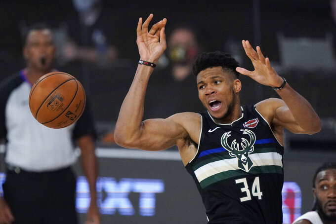 Milwaukee Bucks' Giannis Antetokounmpo (34) reaches for the ball during the second half of an NBA conference semifinal playoff basketball game against the Miami Heat Wednesday, Sept. 2, 2020, in Lake Buena Vista, Fla. (AP Photo/Mark J. Terrill)