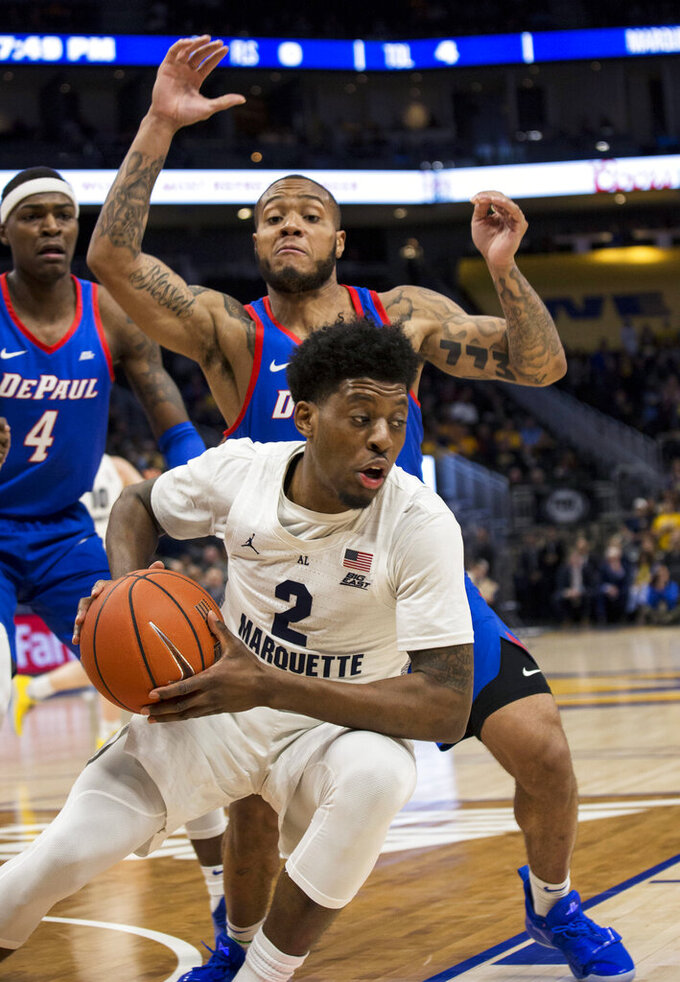 Marquette forward Sacar Anim, front, is defended by DePaul guard Devin Gage, back, during the first half of an NCAA college basketball game, Wednesday, Jan. 23, 2019, in Milwaukee. (AP Photo/Darren Hauck)