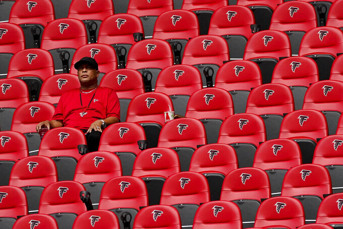 A fan watches play between the Atlanta Falcons and the Detroit Lions during the first half of an NFL football game, Sunday, Oct. 25, 2020, in Atlanta. (AP Photo/John Bazemore)
