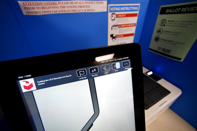 In this Tuesday, Nov. 5, 2019 photo, a touchscreen voting machine and printer are seen in a voting booth, in Paulding, Ga. Georgia's state election board has scheduled an emergency hearing Wednesday, March 11, 2020, to determine whether a county election board violated state laws and election rules when it voted to use hand-marked paper ballots instead of the state's new voting machines for the presidential primary. (AP Photo/Mike Stewart)