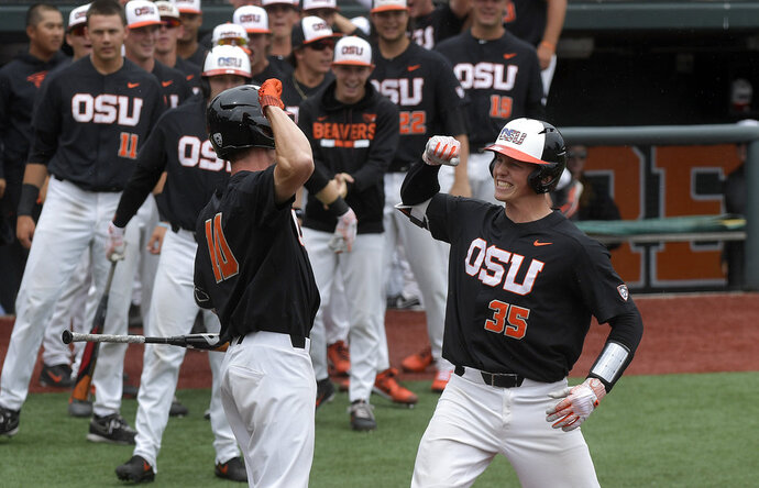 Oregon State's Adley Rutschman (35) celebrates with Micahel Gretler (10) after hitting a solo home run in the opening inning of the first baseball game of the Corvallis Super Regional in Corvallis, Ore., Friday, June 8, 2018. (Mark Ylen/Albany Democrat-Herald via AP)