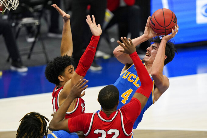 UCLA's Jaime Jaquez Jr., right, shoots against Ohio State's Justice Sueing, left, and E.J. Liddell in the first half of an NCAA college basketball game, Saturday, Dec. 19, 2020, in Cleveland. (AP Photo/Tony Dejak)