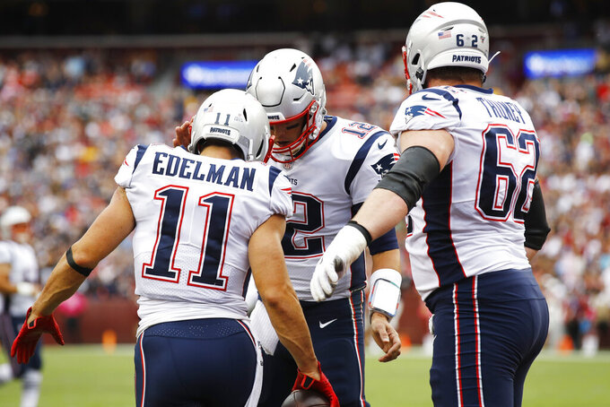New England Patriots wide receiver Julian Edelman (11) celebrates his touchdown with New England Patriots quarterback Tom Brady (12) during the first half of an NFL football game, Sunday, Oct. 6, 2019, in Washington. (AP Photo/Patrick Semansky)