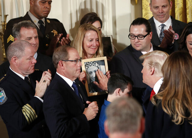 FILE - In this Oct. 26, 2017, file photo, Jeanne Moser, center, of East Kingston, N.H., watches as President Donald Trump reaches out to touch a photo of her son, Adam Moser, during an event to declare the opioid crisis a national public health emergency in the East Room of the White House in Washington. Adam was 27 when he died from an apparent fentanyl overdose. The coronavirus outbreak and the Trump administration's response to the pandemic have been a dominating theme in this year's presidential race. That has overshadowed debate over how to handle the nation's drug overdose crisis, which has contributed to the deaths of more than 470,000 Americans over the last two decades. (AP Photo/Pablo Martinez Monsivais, File)