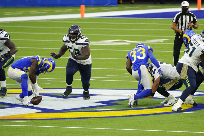 Seattle Seahawks quarterback Russell Wilson, right, fumbles the ball as he is tackled by Los Angeles Rams safety Nick Scott during the second half of an NFL football game Sunday, Nov. 15, 2020, in Inglewood, Calif. The Rams' Leonard Floyd, at left, recovered the ball after the fumble. (AP Photo/Ashley Landis)