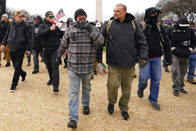 In this Jan. 6, 2021, photo, Proud Boys including Joseph Biggs, front left, walks toward the U.S. Capitol in Washington, in support of President Donald Trump. With the megaphone is Ethan Nordean, second from left. The Proud Boys and Oath Keepers make up a fraction of the more than 300 Trump supporters charged so far in the siege that led to Trump's second impeachment and resulted in the deaths of five people, including a police officer. But several of their leaders, members and associates have become the central targets of the Justice Department's sprawling investigation. (AP Photo/Carolyn Kaster)