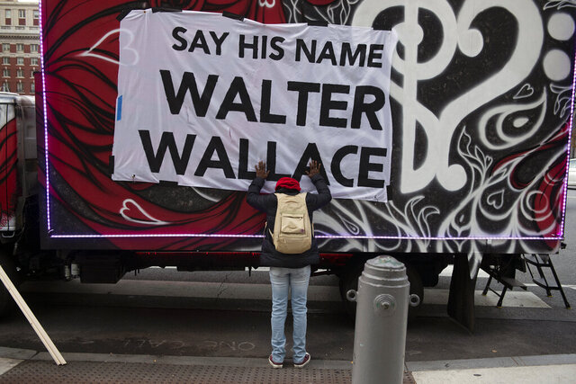 Sheila Rhames rests her hands on a banner honoring Walter Wallace Jr. in Philadelphia, Wednesday, Nov. 4, 2020. Wallace, a Black man, was shot and killed by police in West Philadelphia, last month. Rhames was his neighbor. (Joe Lamberti/Camden Courier-Post via AP)