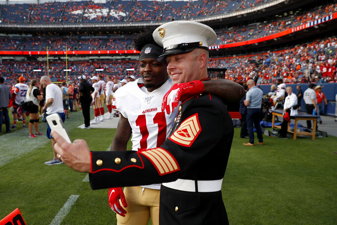 San Francisco 49ers wide receiver Marquise Goodwin (11) takes a selfie on the sidelines with a U.S. Marine during the first half of an NFL preseason football game against the Denver Broncos, Monday, Aug. 19, 2019, in Denver. (AP Photo/David Zalubowski)