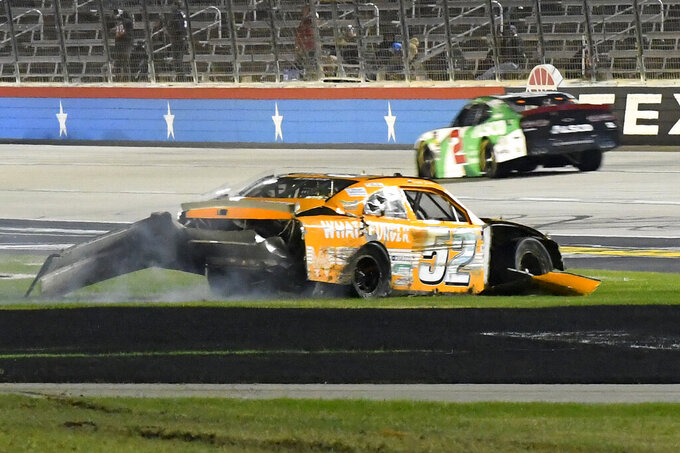 David Starr (52) comes to a rest on the grass after crashing in Turn 4 as Tyler Reddick (2) heads into Turn 1 during the NASCAR Xfinity auto race at Texas Motor Speedway in Fort Worth, Texas, Saturday, Nov. 2, 2019. (AP Photo/Randy Holt)