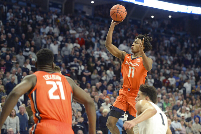 FILE - In this Feb. 18, 2020, file photo, Illinois' Ayo Dosunmu's (11) scores against Penn State in the final minute of an NCAA college basketball game in State College, Pa Watching the shot are Illinois' Kofi Cockburn (21) and Penn State's Seth Lundy (1). The return of stars Dosunmu and Kofi Cockburn has brought a sense of optimism and high expectations to an Illinois program that saw a magical season abruptly halted by the pandemic in March. (AP Photo/Gary M. Baranec, File)