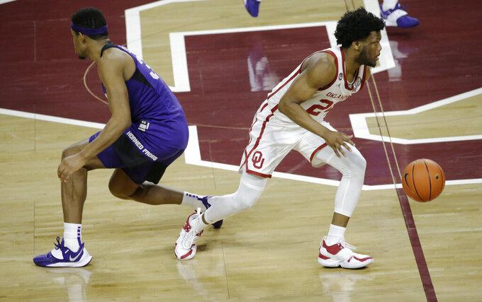 Oklahoma's Elijah Harkless (24) drives the ball past TCU's Kevin Easley Jr. (34) during the second half of an NCAA college basketball game in Norman, Okla., Tuesday, Jan. 12, 2021. (AP Photo/Garett Fisbeck)
