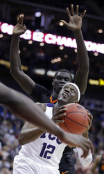 TCU's Kouat Noi (12) shoots under pressure from Oklahoma State's Yor Anei during the second half of an NCAA college basketball game in the Big 12 men's tournament Wednesday, March 13, 2019, in Kansas City, Mo. TCU won 73-70. (AP Photo/Charlie Riedel)