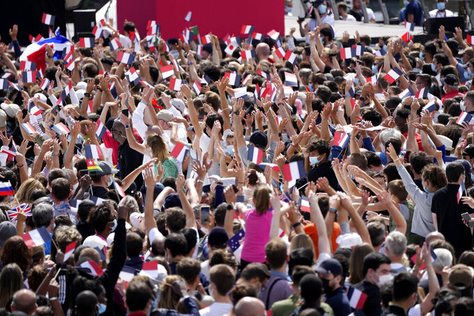 People wave small flags and cheer in the Olympics fan zone at Trocadero Gardens in front of the Eiffel Tower in Paris, Sunday, Aug. 8, 2021. A giant flag will be unfurled on the Eiffel Tower in Paris Sunday as part of the handover ceremony of Tokyo 2020 to Paris 2024, as Paris will be the next Summer Games host in 2024. The passing of the hosting baton will be split between the Olympic Stadium in Tokyo and a public party and concert in Paris. (AP Photo/Francois Mori)