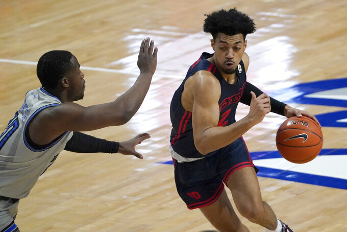 Dayton's Ibi Watson, right, heads to the basket as Saint Louis' Fred Thatch Jr., left, defends during the first half of an NCAA college basketball game Tuesday, Jan. 26, 2021, in St. Louis. (AP Photo/Jeff Roberson)