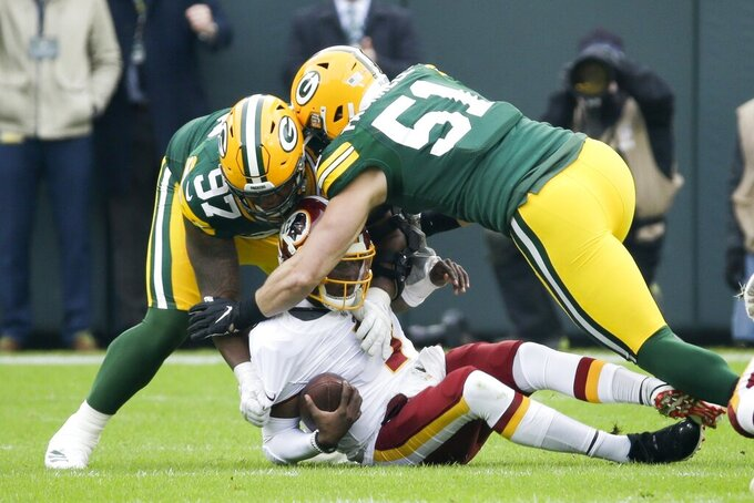 Washington Redskins' Dwayne Haskins is sacked by Green Bay Packers' Kenny Clark and Kyler Fackrell during the first half of an NFL football game Sunday, Dec. 8, 2019, in Green Bay, Wis. (AP Photo/Mike Roemer)