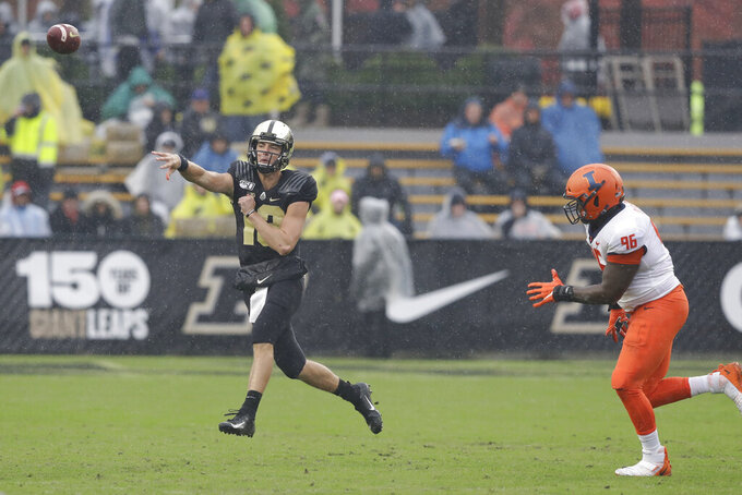 Purdue quarterback Jack Plummer (13) throws while being chased by Illinois defensive lineman Tymir Oliver (96) during the first half of an NCAA college football game, Saturday, Oct. 26, 2019, in West Lafayette, Ind. (AP Photo/Darron Cummings)