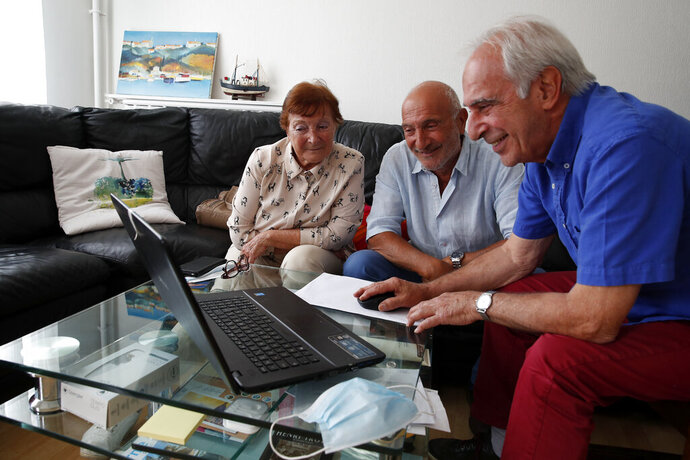 In this photo taken on June 5, 2020, Monette Hayoun, Dr Robert Haiun, and Gilbert Haiun, from left, look at photos of their brother Meyer Haiun on a computer during an interview in Ivry sur Seine, south of Paris. Families whose elders died behind the closed doors of homes in lockdown are filing wrongful death lawsuits, triggering police investigations. One suit focuses on the death of Meyer Haiun, a severely disabled 85-year-old in a Paris home managed by a Jewish charitable foundation headed Eric de Rothschild, scion of Europe's most famous banking dynasty. (AP Photo/Francois Mori)