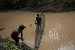 "Agriculture technician Jesus Alfurez holds a sapling for transplanting as he crosses a river helped by a villager, headed to a mining camp where workers use a mercury-less gold-collecting machine, in Madre de Dios, Peru, on April 5, 2019. A study of former gold mines in Peru by scientists at CINCIA and Wake Forest University several years ago found that seedlings transplanted with soil were more likely to survive than ""bare-root seedlings,"" and the use of special fertilizers also helped growth. Some of the trees tested had absorbed trace amounts of mercury through contaminated soil, but it's not clear yet how this will affect them. (AP Photo/Rodrigo Abd)"