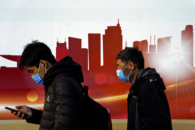 People wearing face masks to help curb the spread of the coronavirus walk by a moral depicting China's skyscrapers along a street in Beijing, Sunday, Dec. 6, 2020. Provincial governments across China are placing orders for experimental, domestically made coronavirus vaccines, though health officials have yet to say how well they work or how they may reach the country's 1.4 billion people. (AP Photo/Andy Wong)