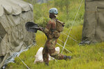 A soldier carries shovels during a rescue operation in Chimanimani about 600 kilometres south east of Harare, Zimbabwe, Tuesday, March, 19, 2019. According to the government Cyclone Idai has killed more than 100 people in Chipinge and Chimanimani and according to residents the figures could be higher because the hardest hit areas are still inaccessible.  Some hundreds are dead, and many more still missing with many thousands at risk from massive flooding in the region of Mozambique, Malawi and Zimbabwe caused by Cyclone Idai. (AP Photo/Tsvangirayi Mukwazhi)