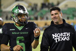 FILE - In this Nov. 15, 2018, file photo, North Texas quarterback Mason Fine (6) laughs about his second-half hand injury with coach Seth Littrell after North Texas pulled out a win against Florida Atlantic during an NCAA college football game in Denton, Texas. Going into Littrell's fourth season, and with two-time C-USA offensive player of the year quarterback Fine one of nine starters back on the league's highest-scoring offense, the Mean Green are again favored in the West Division. (Jake King/The Denton Record-Chronicle via AP, File)