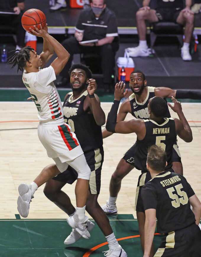 Miami guard Isaiah Wong (2) shoots over Purdue defenders during the first half of an NCAA college basketball game Tuesday, Dec. 8, 2020, in Coral Gables, Fla. (Al Diaz/Miami Herald via AP)