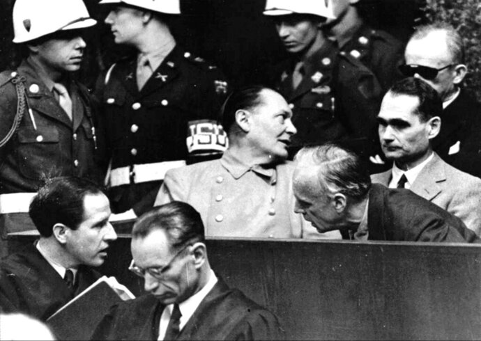 FILE - In this March 27, 1946 file photo, Nazi German Foreign Minister Joachim von Ribbentrop, right, leans in front of Rudolf Hess, Hitler's deputy, to confer with his lawyer, lower left, while Hermann Goering, center, chief of the German air force and one of Hitler's closest aides, turns to talks with Karl Doenitz, rear right, during the Nueremberg war crime trial session. Audio recordings from the historic Nuremberg trials will be made available to the public for the first time in digital form after a nearly two-year digitization process conducted in secret. The files capture around 1,200 hours of the high-profile trial of Nazi leaders in Nuremberg, Germany from 1945 to 1946. (AP Photo, File)