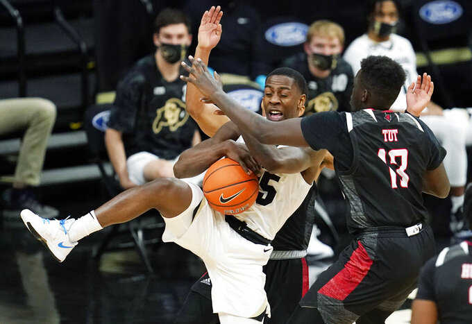 Colorado guard McKinley Wright IV, front left, pulls in a rebound as Omaha forward Wanjang Tut, front right, and guard Ayo Akinwole, back, defend in the second half of an NCAA college basketball game Wednesday, Dec. 16, 2020, in Boulder, Colo. Colorado won 91-49. (AP Photo/David Zalubowski)