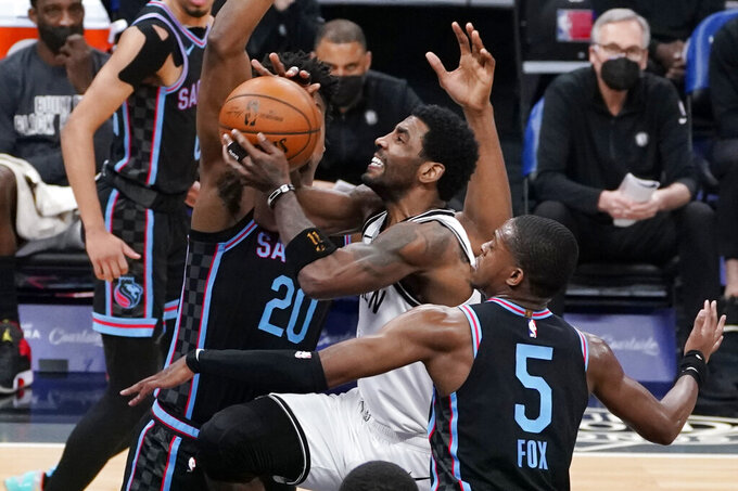 Brooklyn Nets guard Kyrie Irving, center, goes to the basket between Sacramento Kings' Hassan Whiteside, left, and De'Aaron Fox, right, during the first half of an NBA basketball game in Sacramento, Calif., Monday, Feb. 15, 2021. (AP Photo/Rich Pedroncelli)