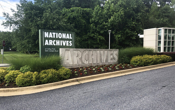 In this Tuesday, June 18, 2019 photo a sign for the entrance to the National Archives is seen in College Park, Md. A Virginia National Guard sergeant is accused of stealing World War II-era dog tags from the National Archives and Records Administration in Maryland, at least the second theft case involving the research facility. Robert Rumsby, of Fredericksburg, Va., told investigators he took dog tags that belonged to four U.S. airmen killed in plane crashes in 1944, according to a criminal complaint filed in federal court last month. (AP Photo/Michael Kunzelman)