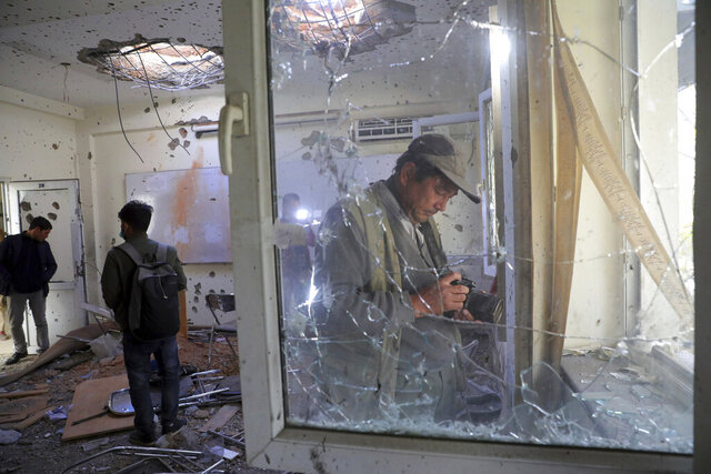 Journalists photograph inside Kabul University after a deadly attack in Kabul, Afghanistan, Tuesday, Nov. 3, 2020. The brazen attack by gunmen who stormed the university has left many dead and wounded in the Afghan capital. The assault sparked an hours-long gun battle. (AP Photo/Rahmat Gul)