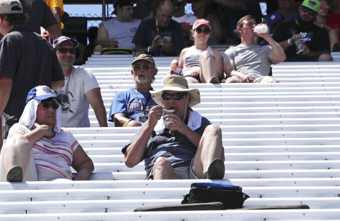 A fan eats ice cream while waiting for driver introductions prior to a NASCAR Cup Series auto race at New Hampshire Motor Speedway in Loudon, N.H., Sunday, July 21, 2019. Temperatures in the area were in the mid-90's during the race. (AP Photo/Charles Krupa)