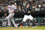 Minnesota Twins' Nelson Cruz (23) scores past Chicago White Sox catcher Zack Collins, off a two-run single by Josh Donaldson during the fifth inning of a baseball game Wednesday, July 21, 2021, in Chicago. (AP Photo/Charles Rex Arbogast)