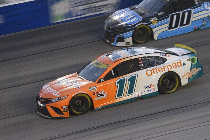 Denny Hamlin (11) races along with Quin Houff (00) in a NASCAR Cup Series auto race Sunday, Sept. 5, 2021, in Darlington, S.C. (AP Photo/John Amis)