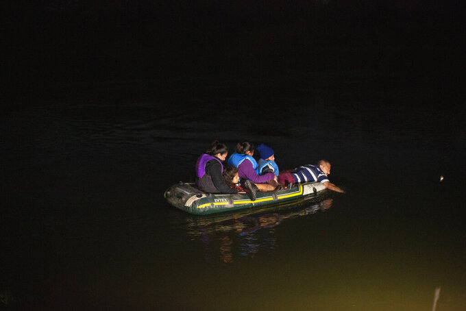 A smuggler takes migrants, mostly from Central American countries, on a small inflatable raft towards U.S. soil in Roma, Texas, Wednesday, March 24, 2021. A surge of migrants on the Southwest border has the Biden administration on the defensive. The head of Homeland Security acknowledged the severity of the problem but insisted it's under control and said he won't revive a Trump-era practice of immediately expelling teens and children. (AP Photo/Dario Lopez-Mills)