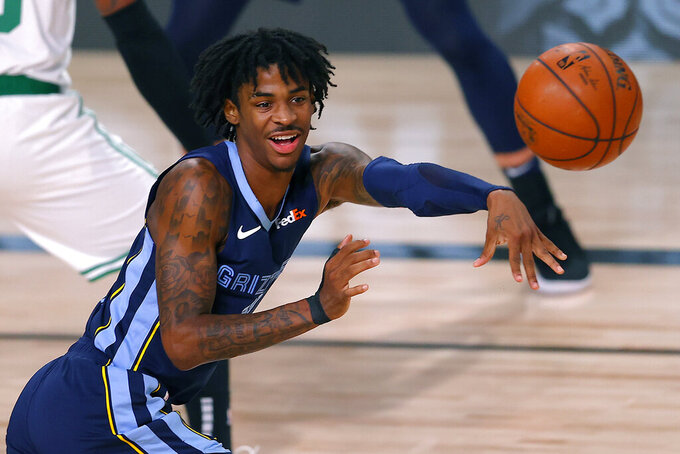 FILE - In this Aug. 11, 2020, file photo, Memphis Grizzlies' Ja Morant passes the ball during the second half of an NBA basketball game against the Boston Celtics in Lake Buena Vista, Fla. Morant and the Grizzlies once again seem to be an afterthought heading into the NBA season. Morant says proving everyone wrong again about him and his teammates is his top goal. (AP Photo/Mike Ehrmann, Pool, File)