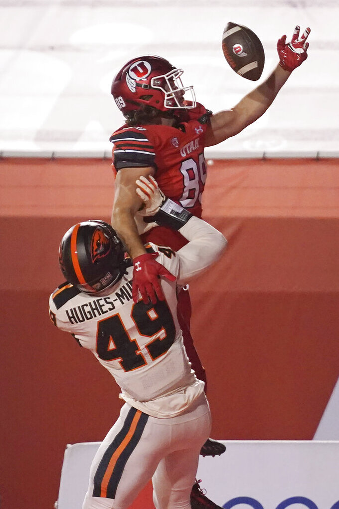 Oregon State linebacker Andrzej Hughes-Murray (49) defends against Utah tight end Cole Fotheringham (89), who catches the ball but lands out of bounds during the first half of an NCAA college football game Saturday, Dec. 5, 2020, in Salt Lake City. (AP Photo/Rick Bowmer)
